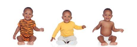 有differents衣裳的三个相等的非洲婴孩 免版税图库摄影