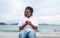 有dreadlocks和白色衬衣键入的消息的非裔美国人的人 库存图片