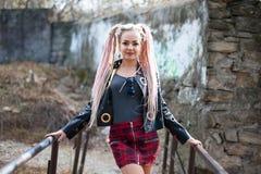 有dreadlocks的一个女孩在皮夹克和一条短裙站立以一个老石墙为背景 免版税库存照片