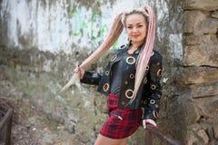 有dreadlocks的一个女孩在皮夹克和一条短裙站立以一个老石墙为背景 免版税库存图片