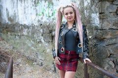 有dreadlocks的一个女孩在皮夹克和一条短裙站立以一个老石墙为背景 图库摄影