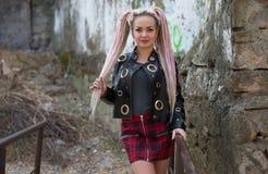 有dreadlocks的一个女孩在皮夹克和一条短裙站立以一个老石墙为背景 库存照片