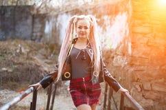 有dreadlocks的一个女孩在皮夹克和一条短裙站立以在b的光芒的一个老石墙为背景 免版税库存照片