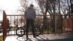 有dreadlocks的一个男孩坐然后开始对乘坐的constraction BMX循环的把戏在滑板公园在a 影视素材