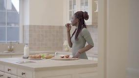 有dreadlocks的俏丽的体贴的非裔美国人的妇女吃一个苹果的在看在窗口的厨房里 照相机 股票录像