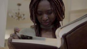 有dreadlocks的俏丽的微笑的非裔美国人的妇女观看在大革龟photobook的照片与她光秃 股票视频