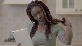 有dreadlocks的俏丽的非裔美国人的妇女从头发去除橡胶和去采取与她的片剂的selfie在 股票视频
