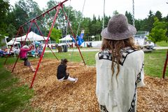有dreadlocks的年轻女人在孩子的摇摆坐在公园 免版税库存照片
