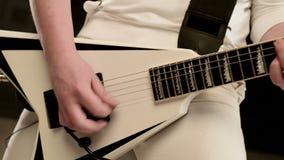 有dreadlocks的特写镜头时髦的独奏吉他弹奏者在他的头和在传神黑背景的白色衣裳 股票录像