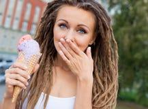 有dreadlocks的美丽的女孩吃五颜六色的冰淇凌的和在街道的一个温暖的夏夜盖她的嘴一棵棕榈 室外 免版税库存图片