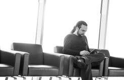 有dreadlocks的英俊的年轻人使用他的在机场休息室的数字式片剂个人计算机,现代候诊室,有背后照明的 库存图片