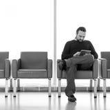 有dreadlocks的英俊的年轻人使用他的在机场休息室的数字式片剂个人计算机,现代候诊室,有背后照明的 图库摄影