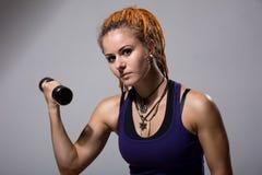 有dreadlocks的训练与哑铃的一个女孩的画象 免版税图库摄影