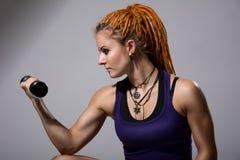有dreadlocks的训练与哑铃的一个女孩的画象 免版税库存照片