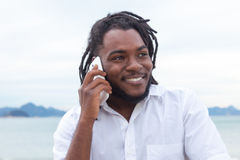 有dreadlocks的非裔美国人的人和在电话的白色衬衣 库存图片