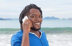有dreadlocks的滑稽的非裔美国人的人在电话 免版税库存照片