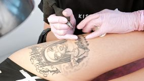 有dreadlocks纹身花刺客户的纹身花刺大师可爱的妇女臀部的女孩的 黑纹身花刺机器和墨水 股票视频