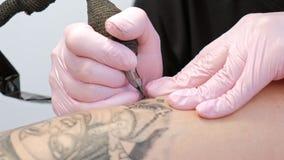 有dreadlocks纹身花刺客户的纹身花刺大师可爱的妇女臀部的女孩的 黑纹身花刺机器和墨水 股票录像
