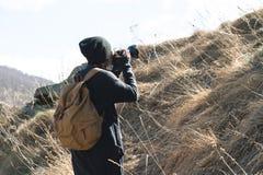 有dslr照相机的妇女行家摄影师拍照片 太阳镜的时髦的女孩有在自然的一台照相机的 免版税库存照片