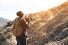 有dslr照相机的妇女行家摄影师 太阳镜的时髦的女孩有在自然的一台照相机的 库存图片