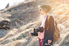 有dslr照相机的妇女行家摄影师 太阳镜的时髦的女孩有在自然的一台照相机的 免版税库存图片