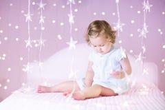 有durly头发的可爱的小孩女孩有桃红色圣诞灯的 库存图片