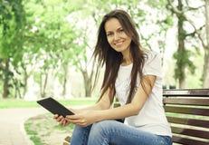 有e书的美丽的女孩在公园 免版税库存照片