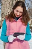 有e书阅读程序的青少年的女孩在公园 免版税库存图片