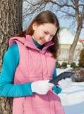 有e书阅读程序的青少年的女孩在公园 免版税库存照片