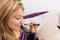 有e香烟和书的女性 图库摄影