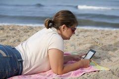 有E读者的妇女在海滩 库存图片