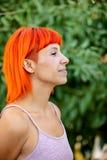有enjoing一轻松的天的红色头发的激动的妇女 库存照片