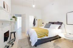 有ensuite和黄色口音的时髦的当代卧室 免版税库存照片