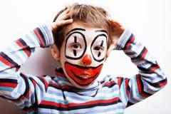 有facepaint的小逗人喜爱的男孩喜欢小丑,哑剧表示 免版税库存图片