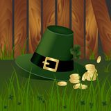 有fhree生叶的三叶草的妖精帽子和在背景的金黄硬币与绿草和木庭院篱芭 圣帕特里克s天 免版税库存照片