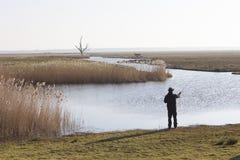 有fishong标尺的孤独的渔夫在荷兰风景 免版税库存图片