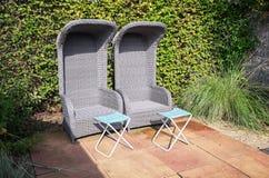 有footbed的两把藤条庭院扶手椅子在庭院里放松 库存照片