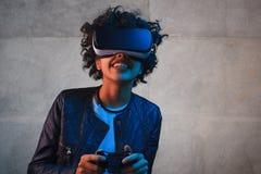 有gamepad和VR风镜的微笑的妇女 库存图片