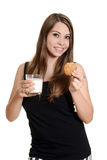 有glas挤奶和麦甜饼的青少年的女孩 免版税图库摄影