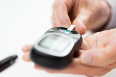 有glucometer的资深妇女检查血糖的 免版税图库摄影