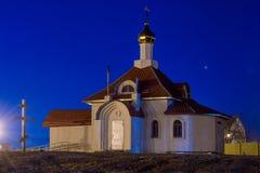 有Golden Dome的正统基督教会在晚上由聚光灯在地面点燃,一个木十字架被埋没 库存图片