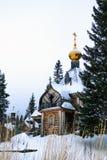 有Golden Dome的老木教会和十字架在冬日 库存照片