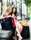 有GPS导航员和行李的两个微笑的女孩 免版税图库摄影
