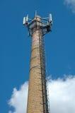 有GSM天线的老工厂烟囱 免版税库存图片