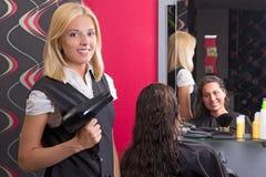 有hairdryer的美发师和美容院的微笑的顾客 库存照片