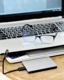 有hdd灰色和眼镜的笔记本灰色现代黑键盘 免版税库存照片