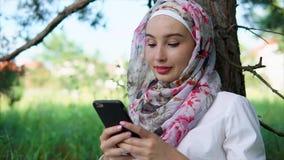 有hijab的一名妇女聊天与智能手机的朋友的夫人在公园 股票录像