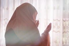有hijab祈祷的回教妇女室内在明亮的窗口 库存照片