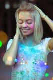 有Holi油漆的喜悦的白肤金发的妇女在她的摆在与col的面孔 免版税图库摄影