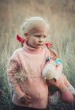 有hourse玩具的可爱的哀伤的女孩在公园 库存图片